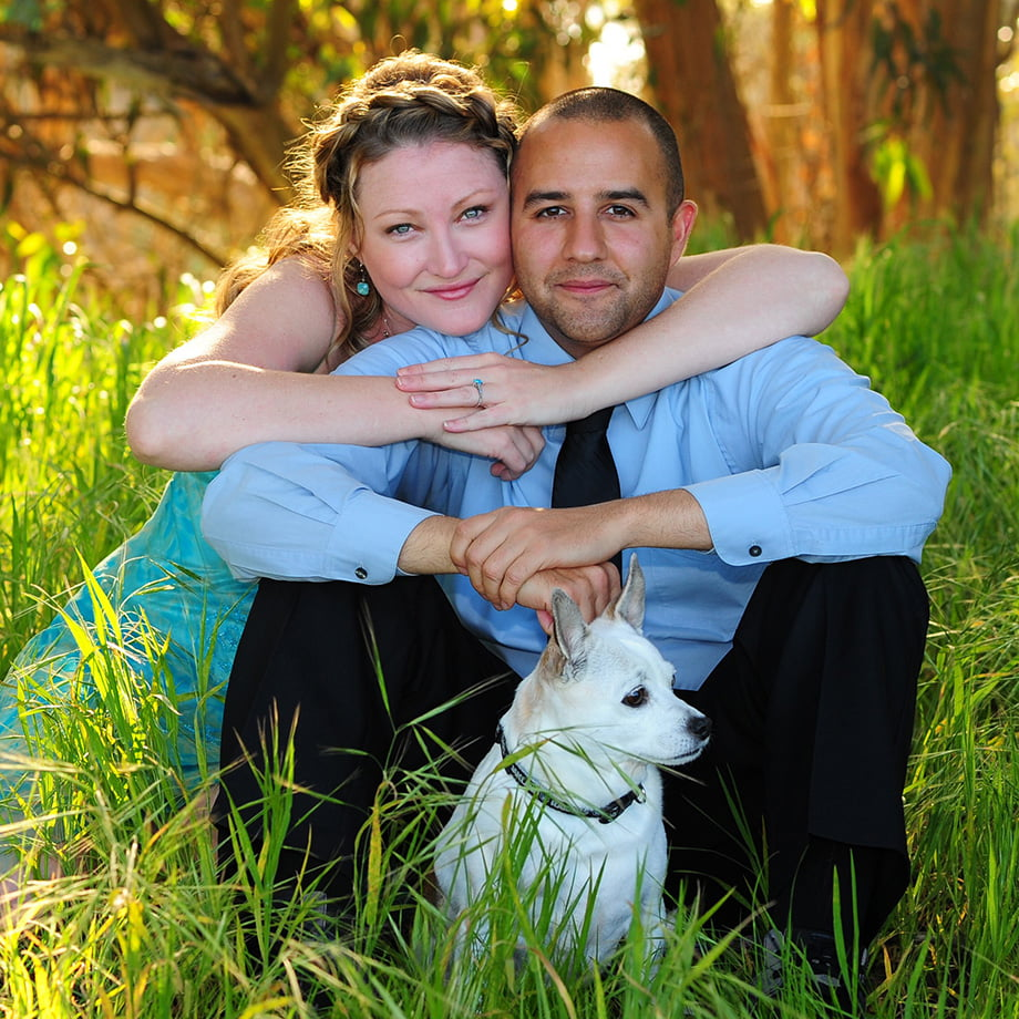couple in grass with dog