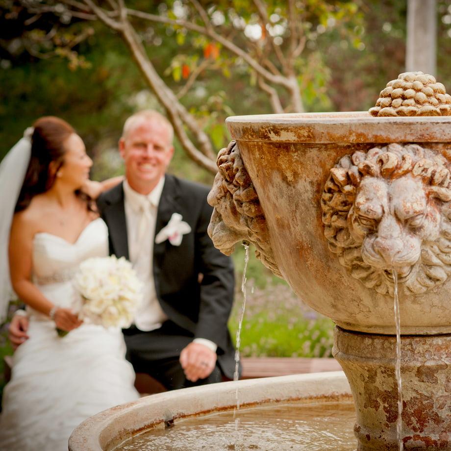 bride and groom near fountain