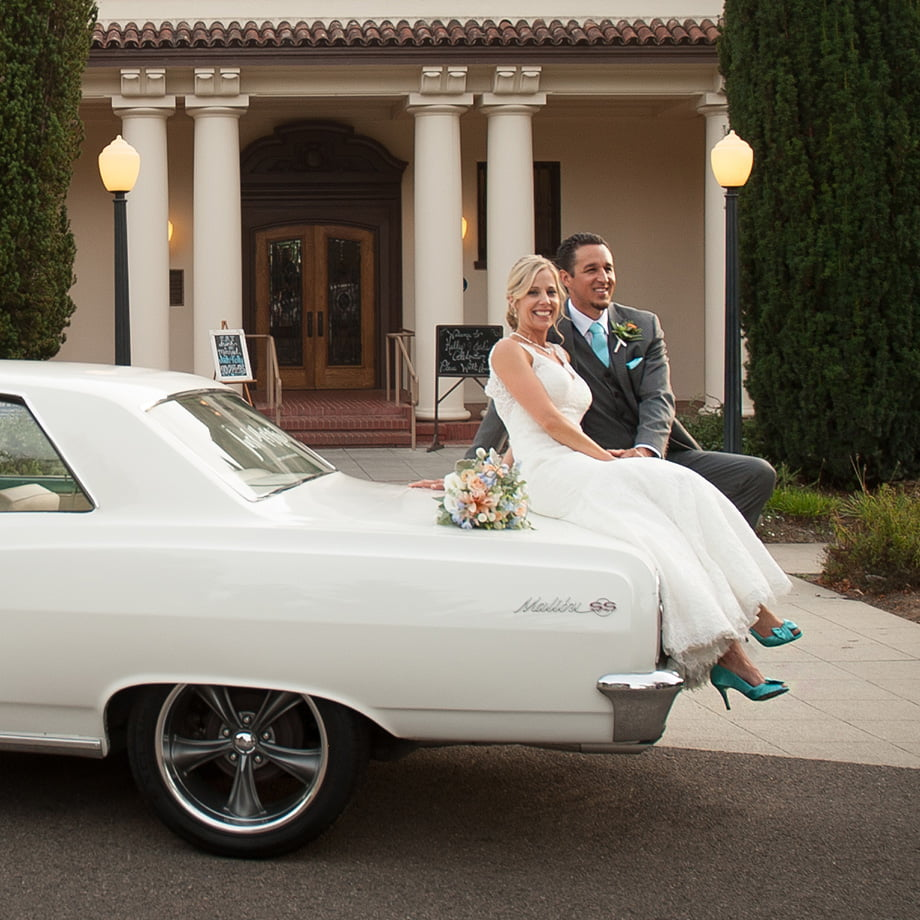 bride and groom sitting on classic car